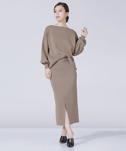 モード感たっぷりのとろみカラーのセットアップは、ボートネックのトップスとベルトが付いたスカートで女性らしいシルエットに。