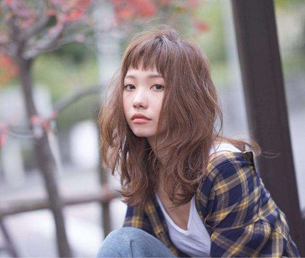 短めバングがかわいらしいヘアスタイル。レイヤーの入った毛先にゆるくパーマをかけ外国の少女のような印象に。