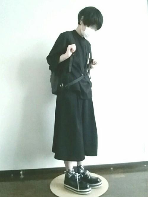 黒のTシャツとドレープガウチョパンツ、小物も黒で統一してつくるクールなオールブラックコーデ。厚底シューズの白黒のボーダーがワンポイントとなっています。足首を出すことで、コーデが重くなりすぎないように。
