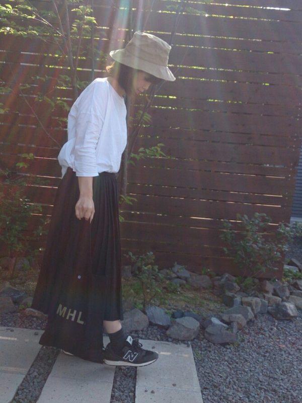 黒のプリーツスカートを使ったコーディネートです。コットンバッグとシューズ、靴下が黒なので、トップスには白を持ってきて明るさをプラスして。ベージュのハットが春らしいですね。
