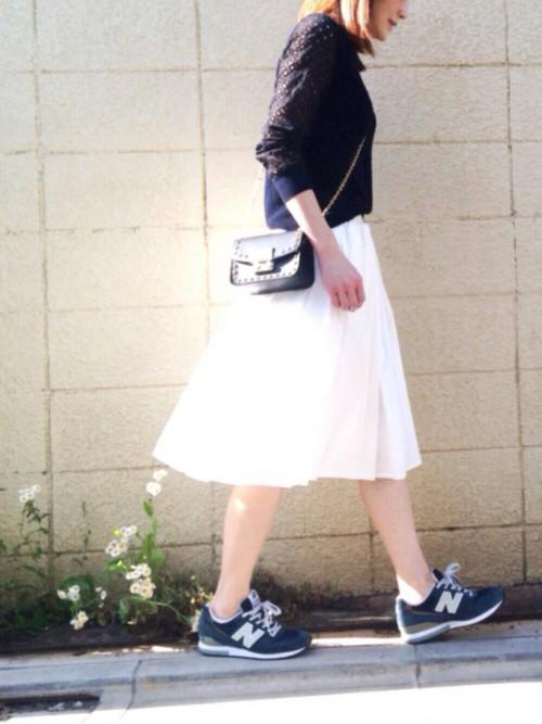 白いフレアスカートは、ネイビーのスニーカーできれい目カジュアルに。素足を出して抜け感のあるコーデが春らしい。