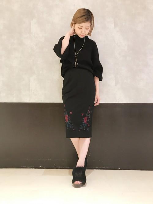 長めのタイトスカートの裾に近いサイド部分にシンメトリーに刺繍が入ったスカート。刺繍の位置が絶妙なので、脚が細くスタイルよく見せる効果を上げています。シンプルにブラックニットに合わせたIラインのコーディネート。