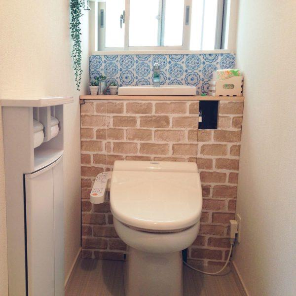 タンクレスDIYを施したトイレ。優しいカラーのレンガシートと白×ブルーの手ぬぐいで、ナチュラルで素敵なトイレの完成です。