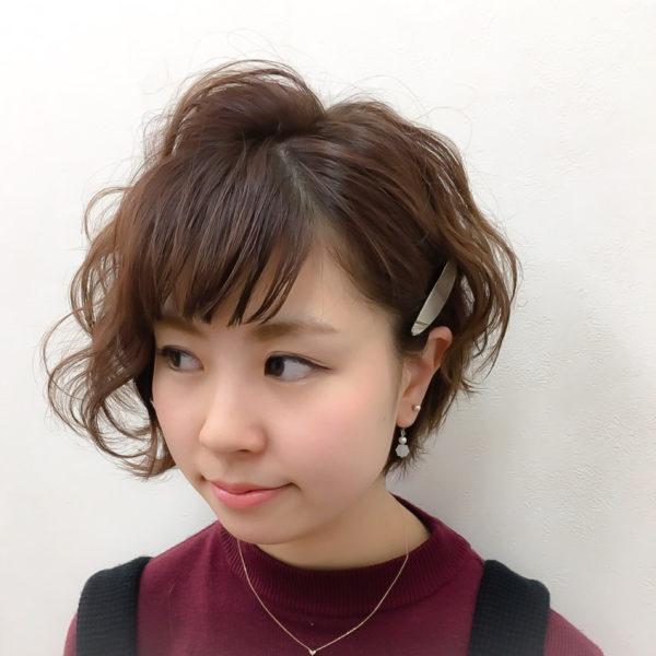 ワンサイドを耳に髪をかけて、片方をふわふわパーマスタイルというアシンメトリーなヘアスタイル。バングの分け目の三角形が丸顔対策になって、スッキリした小顔に見えますね。