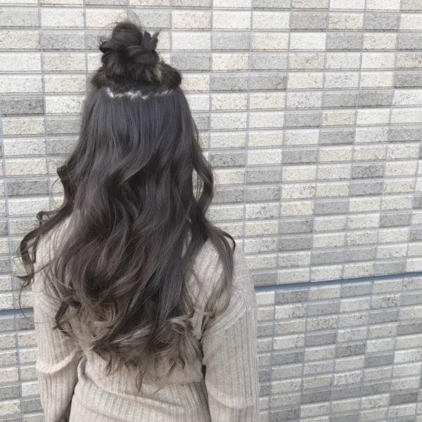 ルーズに取り上げた髪の毛をゆるく三つ編み。お花のような形に整えて個性的なキュートスタイルに。