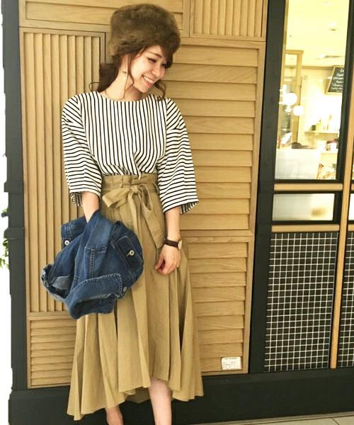 裾線が前後で違うイレギュラーヘムのスカートで脚がより美しく見えるタイプ。定番のベージュでもキュートに演出。ハイウエストとリボンでアクセントをつけて。