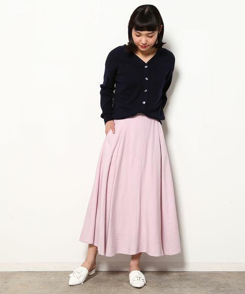 甘さ控えめのピンクフレアスカートは、Vネックのネイビーカーディガンをトップスに。白いフラットパンプスに合わせてカーディガンを黒に変えても◎。