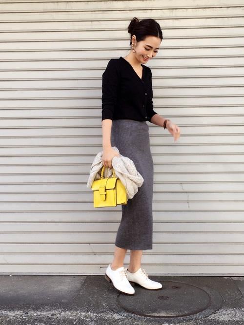 黒のVネックニットとグレーリブスカートの大人シンプルコーデ。春を思わせる黄色のハンドバッグが素敵です。