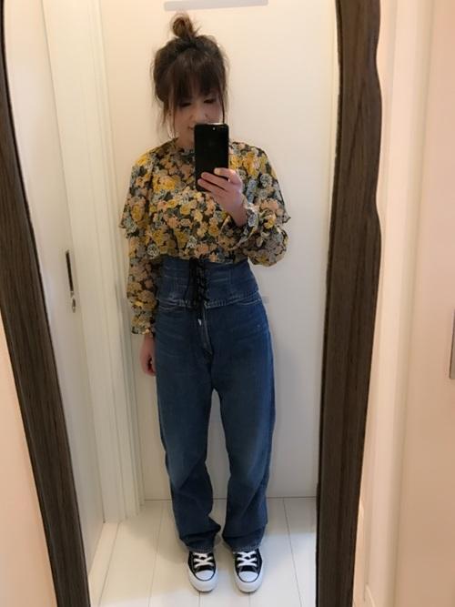 花柄プリントのシャツにデニムのコルセットベルト。個性的で甘すぎない雰囲気になっています。