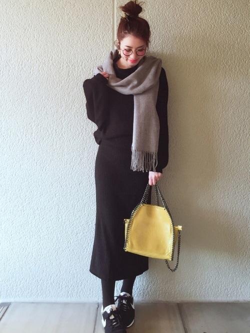 黒のニットとリブスカートのセットアップ風コーデに、グレーマフラーをふんわり巻いています。黄色の個性派バッグがキュートなアクセント。