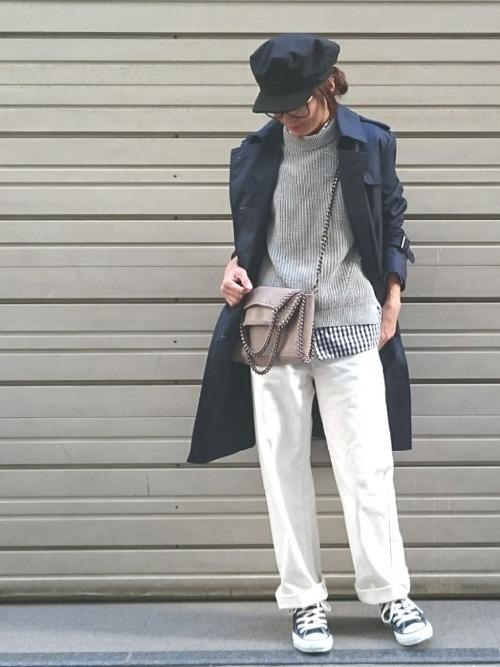 ロールアップしたホワイトデニムにネイビートレンチを羽織ったスマートな着こなし。