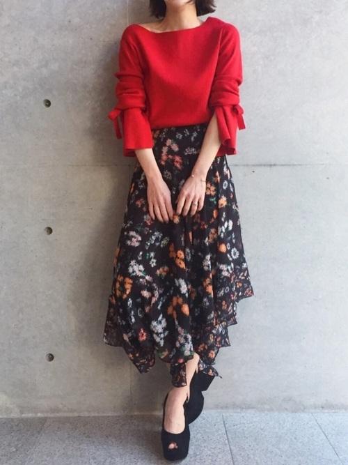 スカートのヘムライン、オープントゥサンダルや袖のリボンが印象的な赤のニットが、フラメンコを思わせるスカートコーデ