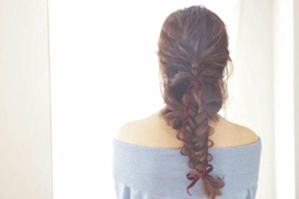 ハーフアップでまとめた髪を、サイドから持ってきた髪とリボンでまとめてから編み込みで束ねたスタイル。一見、複雑な編み目が難しそうにみえるけど、順番にしていけば思ったより難しくないヘアアレンジです。