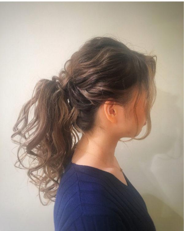 巻いた髪をくしゅくしゅっと無造作に結んだヘアアレンジ。タイトにまとめるとポニーテールは学生っぽくなりがちなので、ふわふわ感のボリュームを大事にして。