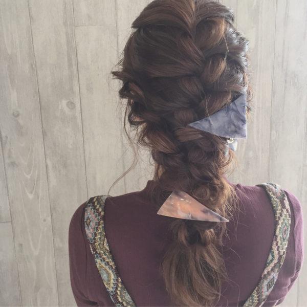 トップからゆるく編み込んだ可愛らしい雰囲気のヘアスタイルです。大きめの三角クリップとバレッタをつけるとアクセントになります。