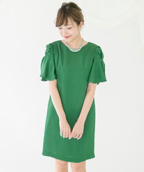 初夏を思わせる鮮やかなグリーンのワンピース。袖にもデザインがあるので、少しのアクセサリーで十分華やいだ装いに。