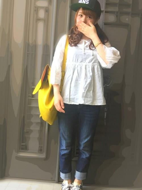 白のガーリーなブラウスと合わせたデニムコーデに黄色のリュックを肩掛けしています。黄色はキュートな差し色になりますね!