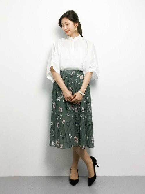 フレアスリーブにスタンドカラーの白いブラウスがオリエンタル風でフォークロアな雰囲気。グリーンのプリーツスカートに花を散らしたプリントで上品な印象のアイテムです。大人のレディスタイルに。