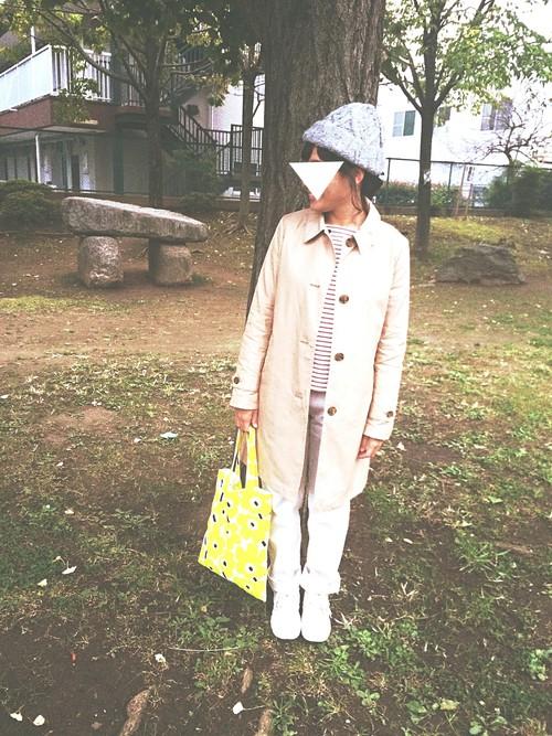 ボーダーのトップスにチノパン、ステンカラーコートの無難コーデに模様編みのニット帽、個性的な手提げなどの小物で、自分らしさをプラス。