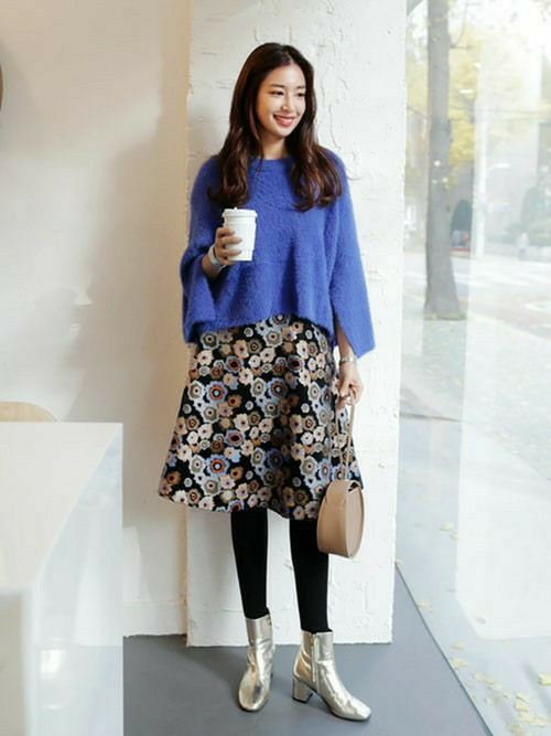 袖の切り込みがポイントのブルーニット。花柄のスカートにシルバーのブーツの組み合わせがレトロな雰囲気をプラス。