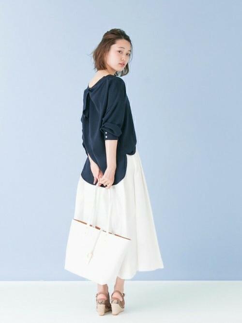 背中の空いたトップスは、今年注目のアイテム。ハリのあるチノスカートでAラインを作って女性らしく。