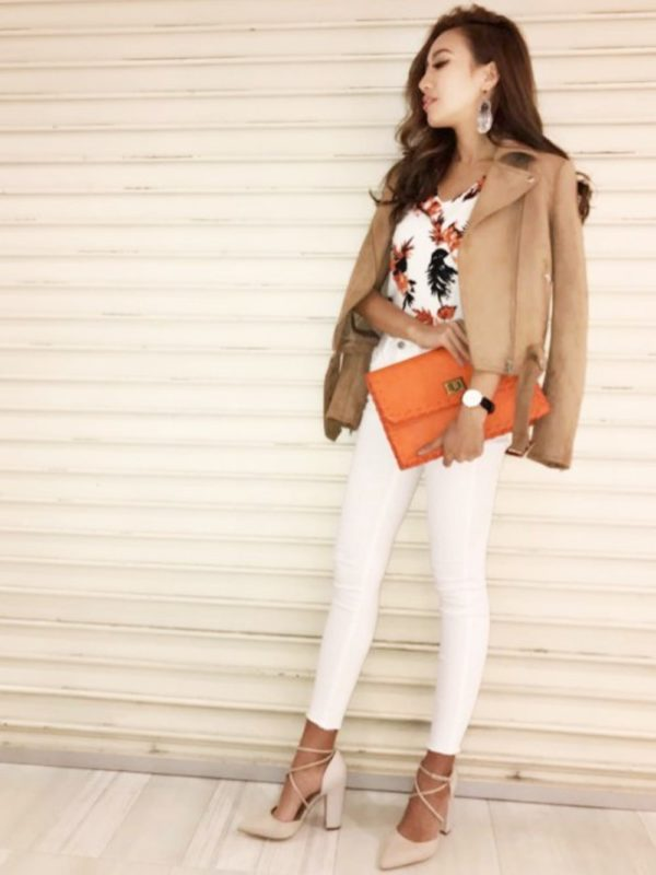 フラワープリントのブラウスにオレンジのクラッチバッグとブラウン系のジャケットをコーデ。同系色のカラーなので統一感があります。