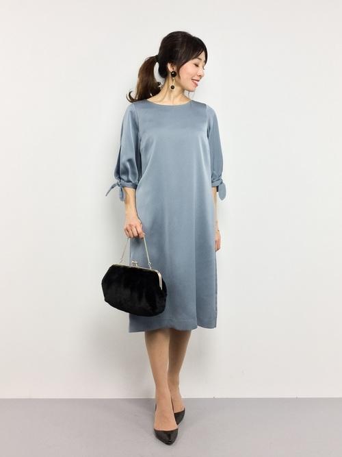 光沢のあるサテンのワンピース。シンプルなデザインの上、グレイッシュなブルーなので派手になり過ぎず、シックに着こなせます。黒の小物で引き締めて。