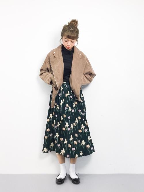 おくれ毛のあるおだんごヘアに黒いトップス、花柄スカートは、レトロカジュアルな雰囲気になりますね。ピーチスキンのライダースジャケットも雰囲気によくあっています。白いソックスもポイントですね。