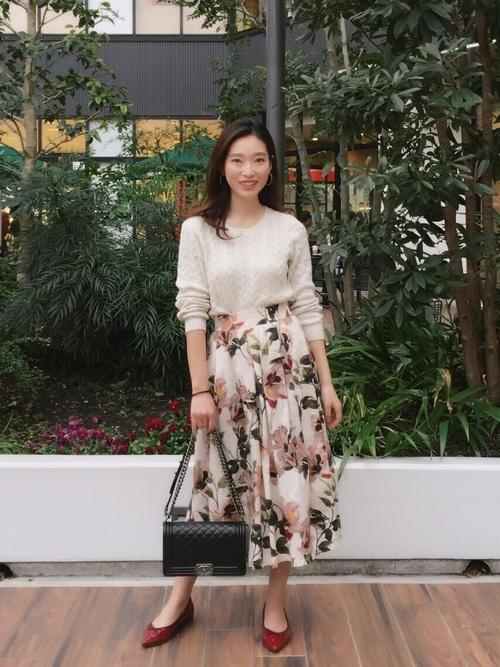 大きな花柄が大人っぽいスカートはトップスはシンプルにして、赤いパンプスでフレンチ感を出すとトレンドスタイルになりますね。ニットもしっかりウエストインするのがスタイルアップも叶いますしスタイルアップも叶いますしトレンドのシルエットになります。