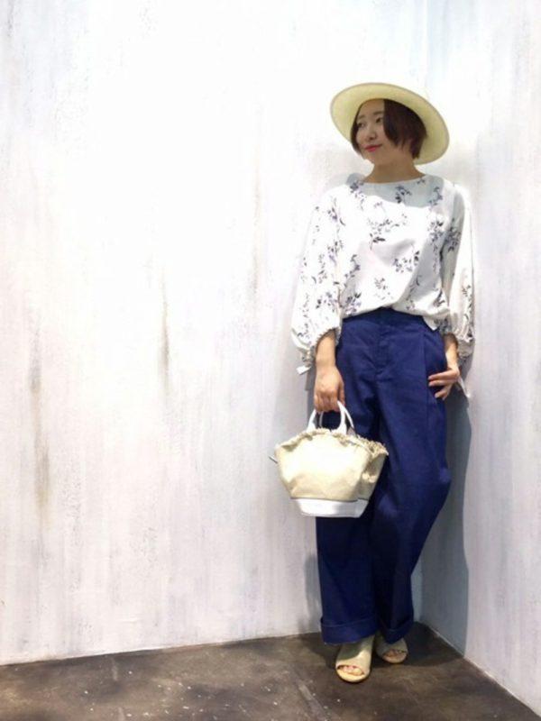 ホワイトをベースにしたフラワープリントのブラウスと、ブルーなパンツで爽やかに仕上げています。麦わら帽子が春めいていますね。
