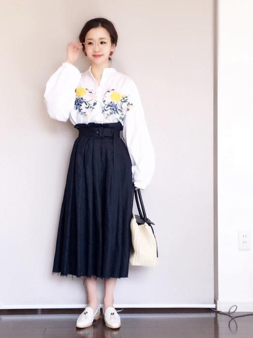 品のある紺のプリーツスカートと合わせてエレガントな印象に仕上げていますね。シニョンなどのまとめ髪にフォーマルフレームの眼鏡で、きれいめな雰囲気です。黄色の花がキュートに映えますね。