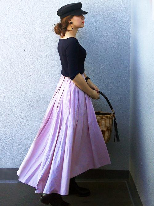 キレイなラベンダー色のスカートを黒の小物で引き締めて。かごバッグで軽やかさを出しています。