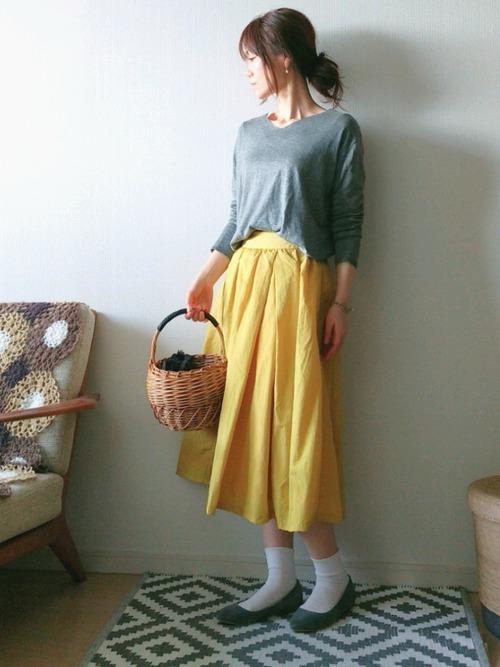 ライトグレーのニットにイエローのスカートの組み合わせ。黒やチャコールグレーよりもきつくなり過ぎず、柔らかな印象です。
