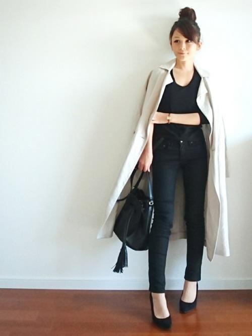 ブラックで統一したトップス&ボトムにトレンチコートを合わせたクールな着こなしですが、細いベルトの時計やパンプスを履いた足元に、女性らしさを漂わせたoutfitになっています。