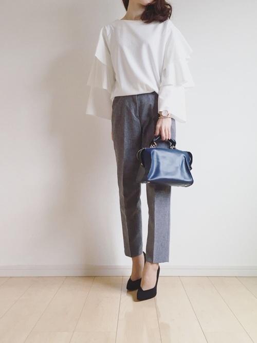 グレーとホワイトというシックな色合いのコーデに、ネイビーのバッグを持って通勤コーデに。でもブラウスのディテールが個性的。