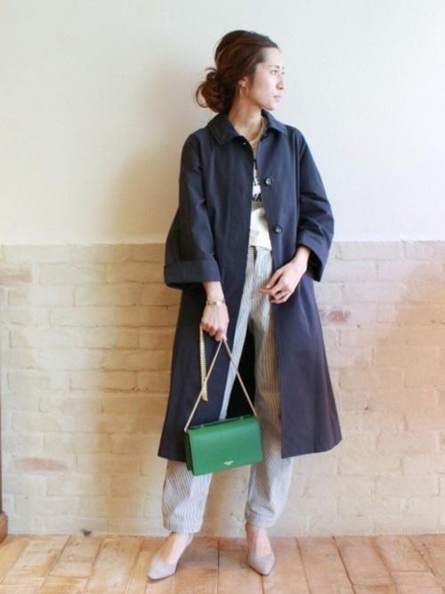 ラフなパンツスタイルの上にトレンチを羽織って、春を感じさせるグリーンの上品バッグでお出かけコーデに。