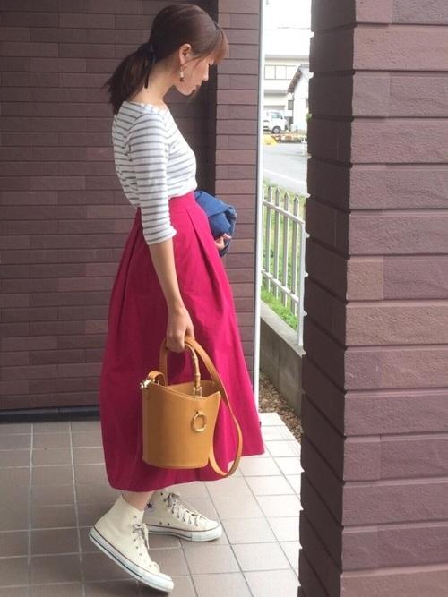鮮やかなショッキングピンクのスカートは、シンプルな白ベースのボーダートップスと、白のコンバーススニーカーでカジュアルに着こなすのがおすすめ◎ショッキングピンクは、着こなしが難しそうですが、とってもおしゃれに決まっていますね☆