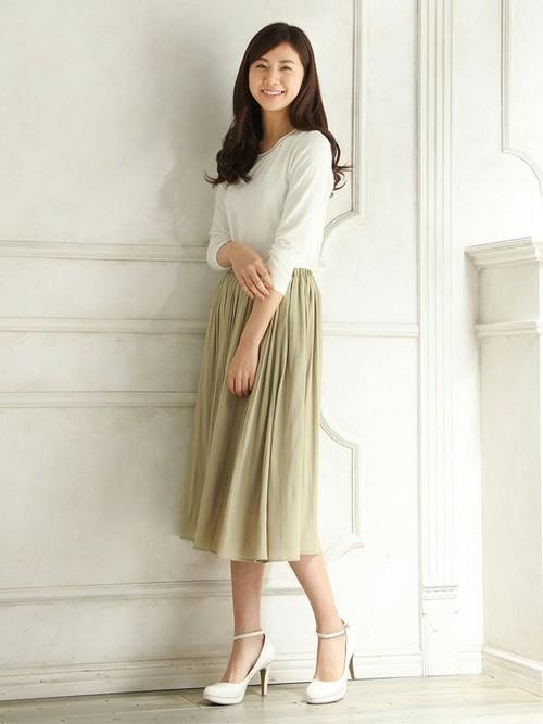 春らしい素材のスカートはナチュラルな色合いが魅力。白を合わせて女性らしいスタイルに仕上がっています。
