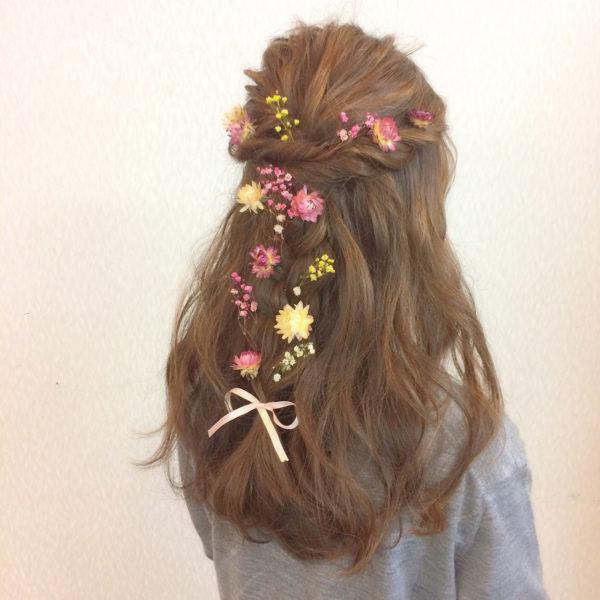 ハーフアップにイエロー、ピンクのガーリーな小花をつけると若々しく元気な印象に。