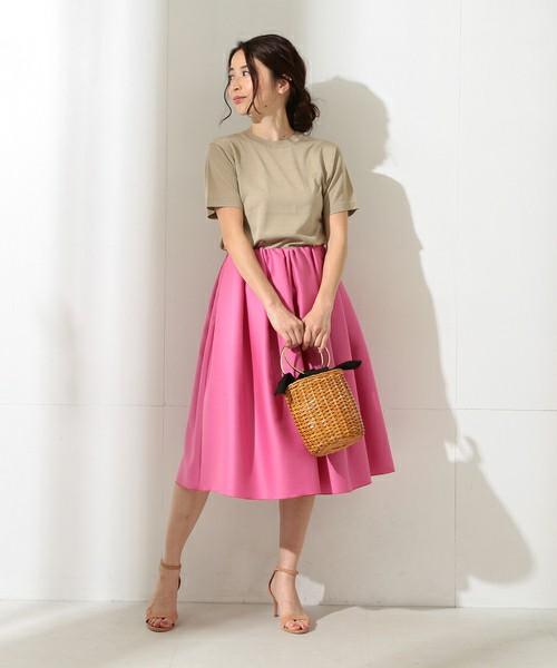 シルクウールのピンクタックスカートは落ち着いたアースカラーのTシャツと合わせて。ヒールサンダルとかごバッグできれいめの初夏コーディネートに。