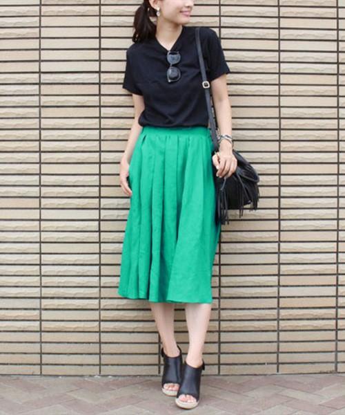 ブライトグリーンのスカートをメインに、あとは黒でまとめて。レディライクなひざ丈スカートを、サングラスやフリンジバッグで甘辛ミックス。