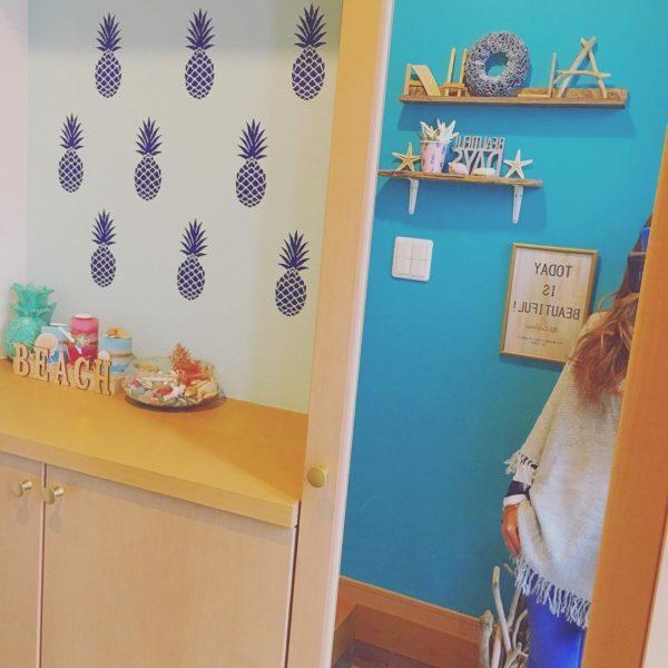 壁を爽やかなブルーでペイントした玄関。小さな棚を使ったディスプレイスペースには、スターシェルや貝殻を飾ってさらにビーチスタイルを印象づけています。流木など素材を変えて作ったALOHAの文字が個性的ですよね。ニッチ部分のパイナップル柄はハワイアンな雰囲気。