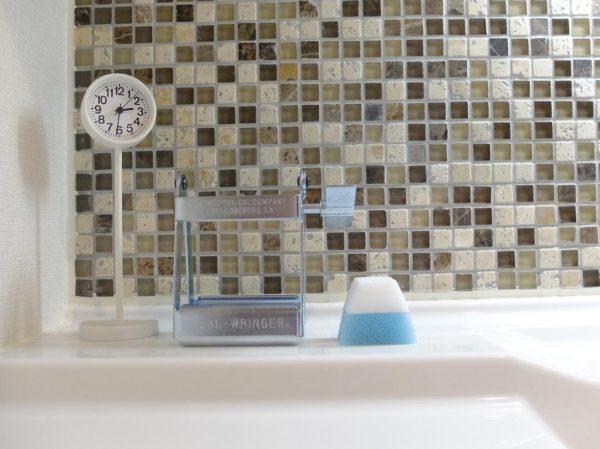洗面所の壁にモザイクタイルを貼った実例。色味がホワイトからブラウンのグラデーションで落ち着いた雰囲気を演出しています。こちらは小さな正方形のタイルですが、表面の素材感が違うものが入っているので、均一ではなく遊び心が出ていますね。