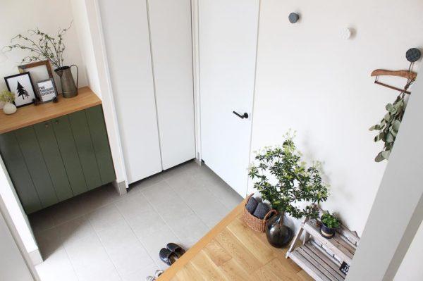 植物のグリーンと木目のベージュが、壁と玄関タイルの白に映えて洗練されたイメージに。靴箱の上や廊下に置いてあるアイテムもまとめているので統一感がありますね。片付け上手なんだなと思わせてくれる玄関です。