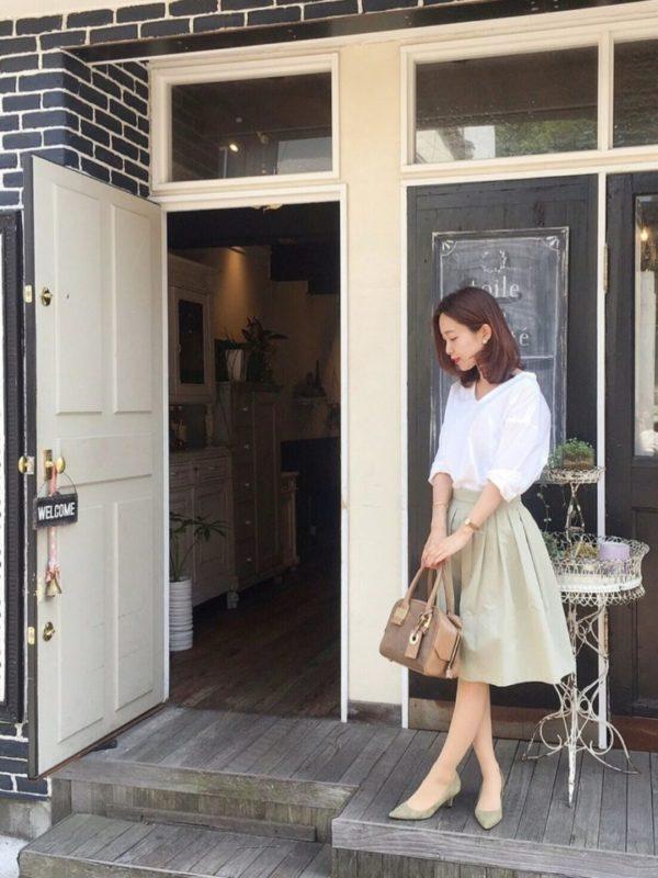 白シャツとAラインのスカートを使用した春らしいコーディネート。全体の色バランスが絶妙!全体的にくすみがちな色合いを白のシャツを取り入れることでバランス良くスタイリングされています。