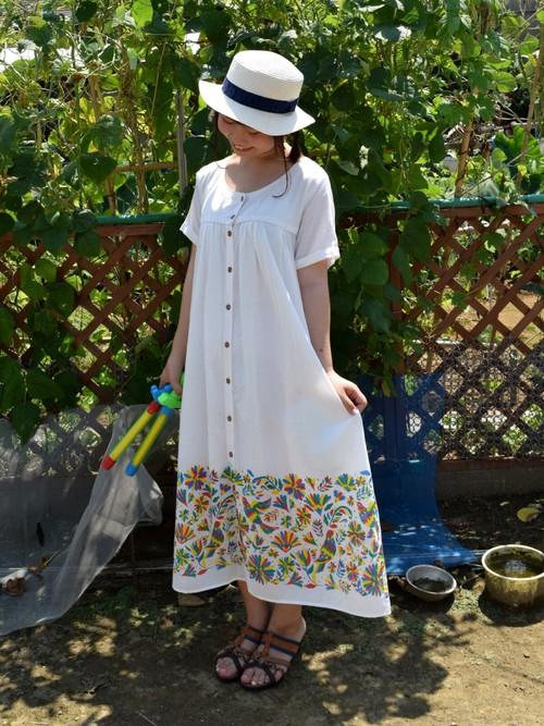 清楚なイメージの半袖の白いワンピース。裾部分に入ったカラフルなモチーフが良いアクセントとなっていて、おしゃれ度がアップしていますよね。夏らしさがアップする帽子やサンダルとあわせたコーディネートです。