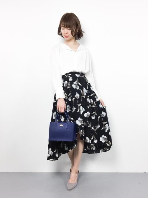 白い花柄がぱっと目立つこちらのスカートは、歩くたびに足の見え方が変わり、より美しく見せてくれます。花の色に合わせて白いシャツを合わせると清楚感が増します。きれいな青の小さめバッグがいいアクセントに。