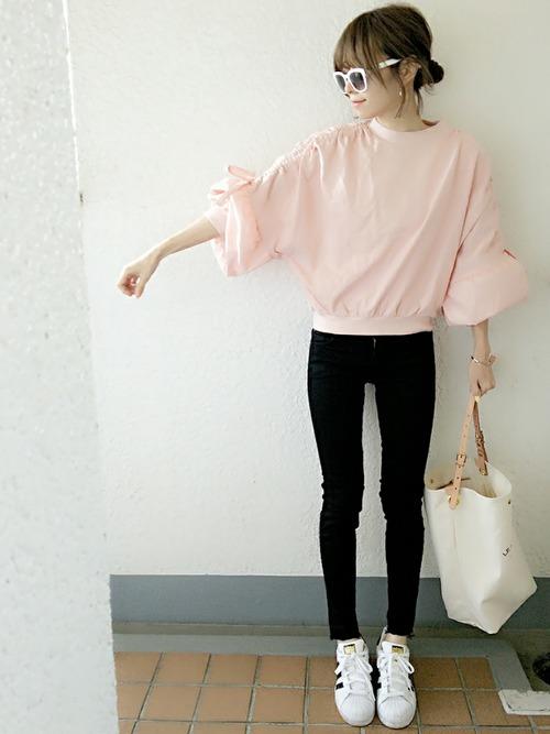 ふんわりスリーブが可愛いピンクのスウェットトップス。袖のリボンでシルエットに変化をつけた着こなしを楽しんで。