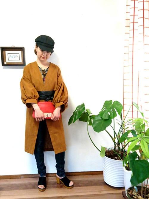 茶系のふんわりとしたバルーンスリーブのアウターが印象的なコーデ。帽子とベルトとシューズは黒でまとめてクラッチバッグを赤でアクセントにしています。