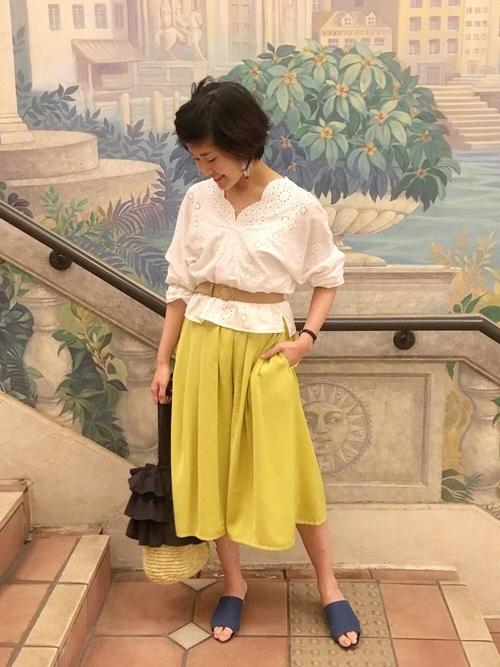 ホワイトレースブラウスにイエローのカラースカートを合わせて春の日差しのような軽やかなコーディネートに。デニムのサンダルも春らしいアイテムです。ブラウスの上からウエストマークしてスタイルアップも。